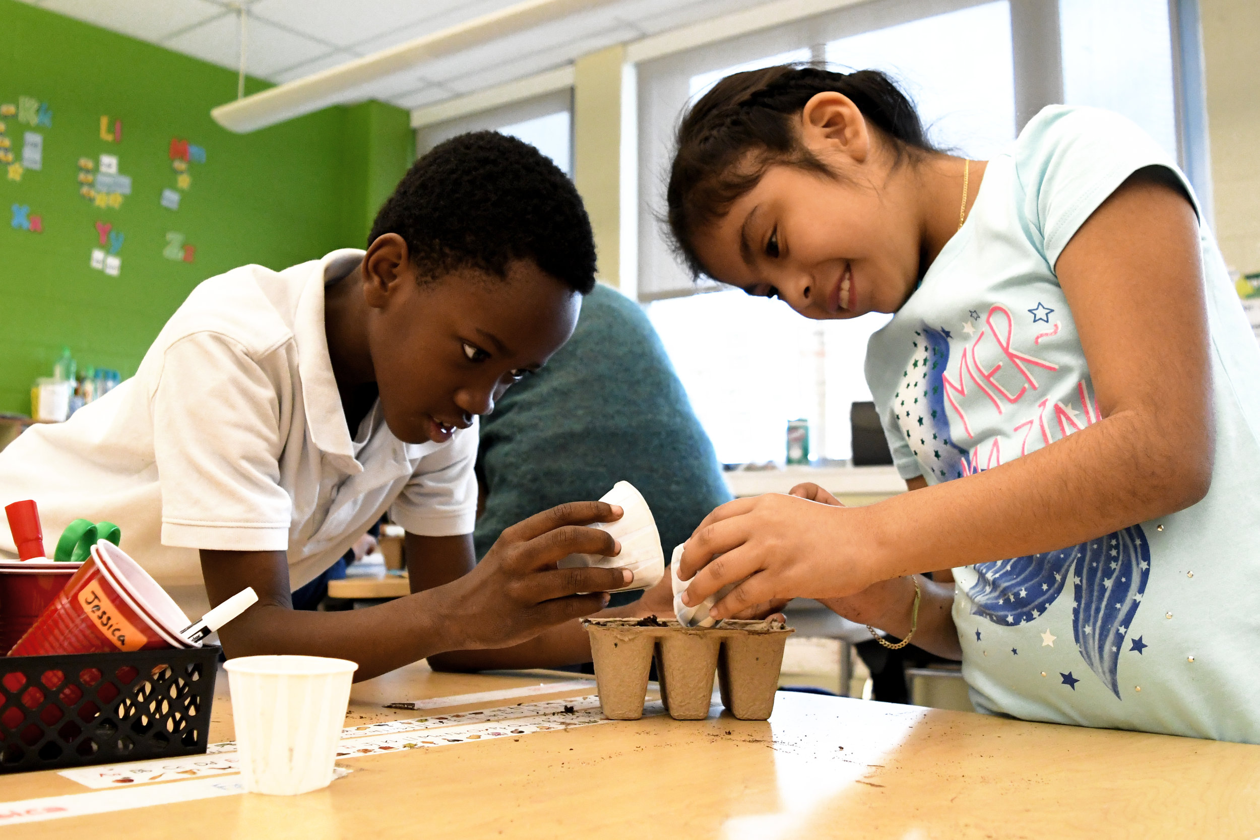 Students at Seaton Elementary in Washington, D.C., plant flowers for their school's garden.