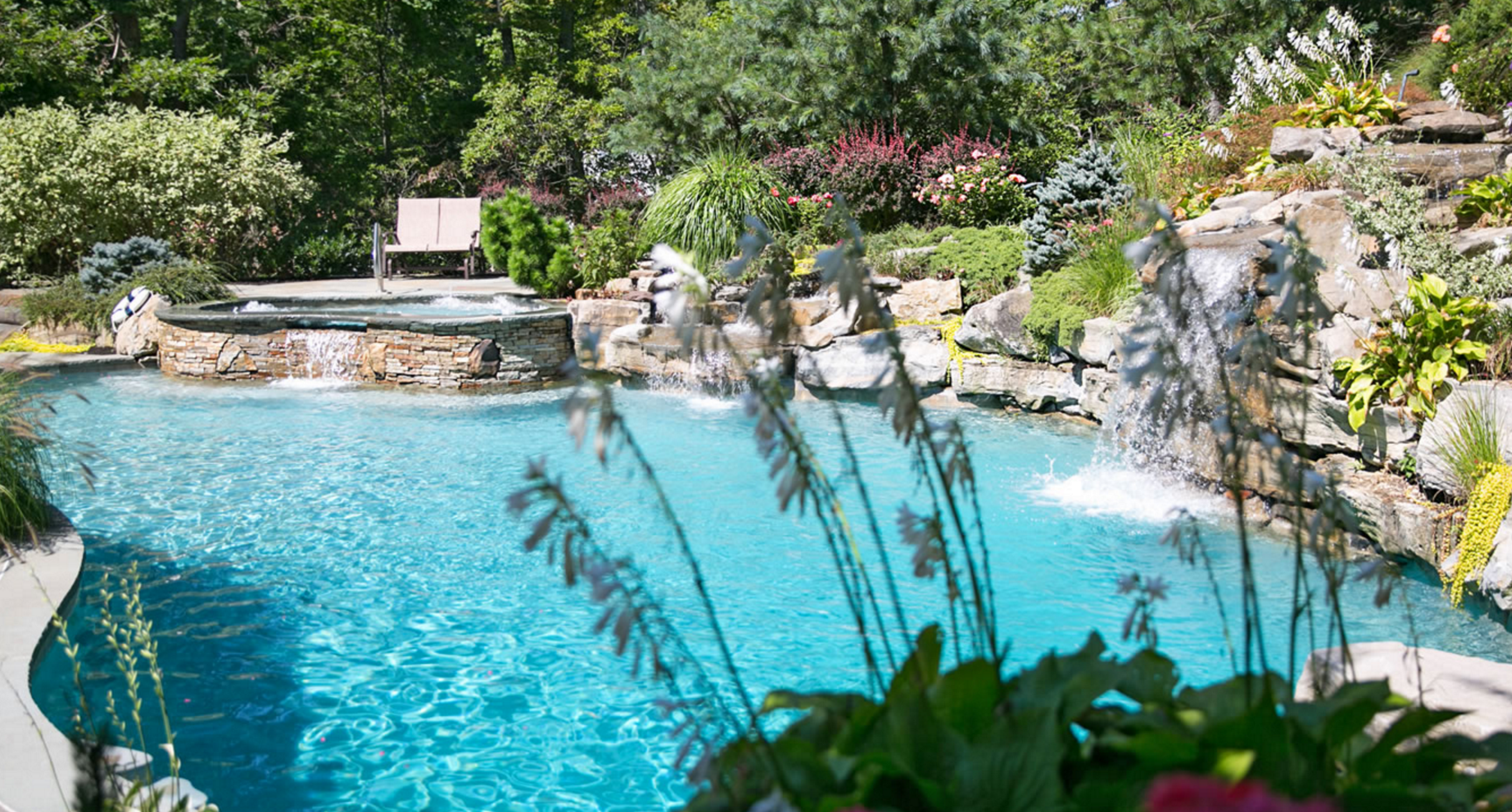 This freeform gunite swimming pool features a built-in spa, waterfall, and lush plantings. Designed and installed by Platinum Site Development in Long Island, NY.