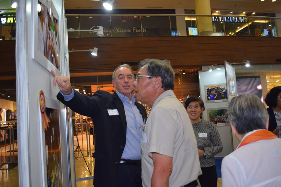 John Chua looking at one of the photos in the exhibit. Photo courtesy of Amcham Foundation.