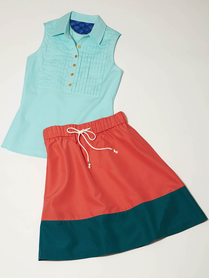 women's light blue short-sleeved golf top with salmon colored golf skirt
