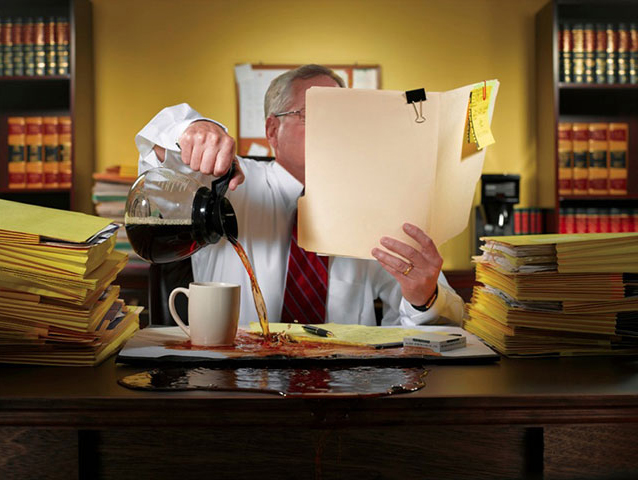 Image of man over pouring coffee onto his desk.
