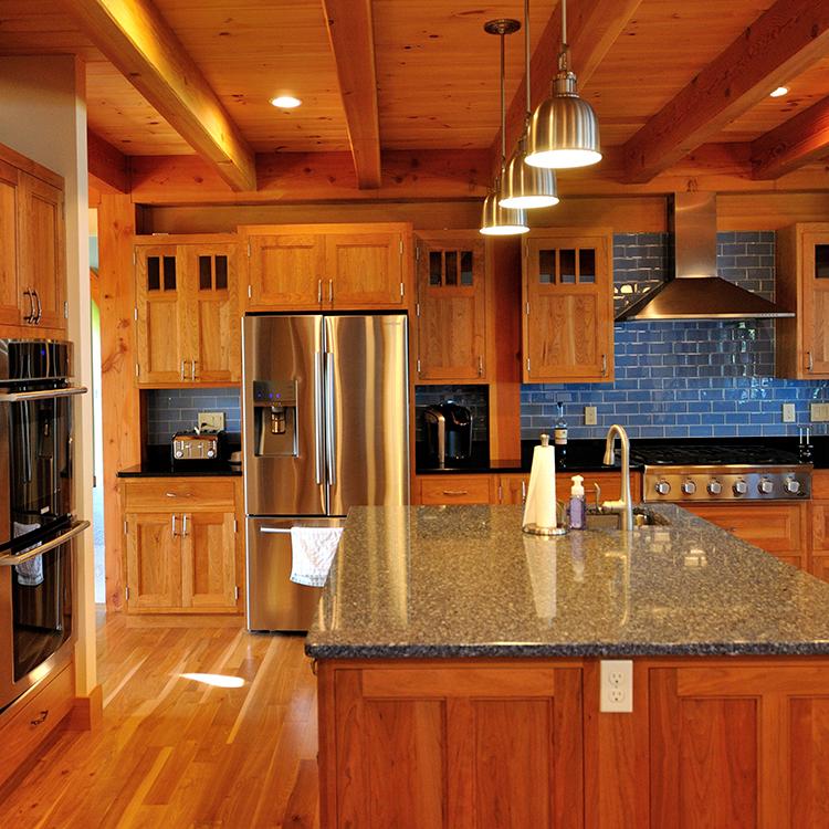 Double ovens, paneled island, Cambria quartz top, bar sink, pendant lighting