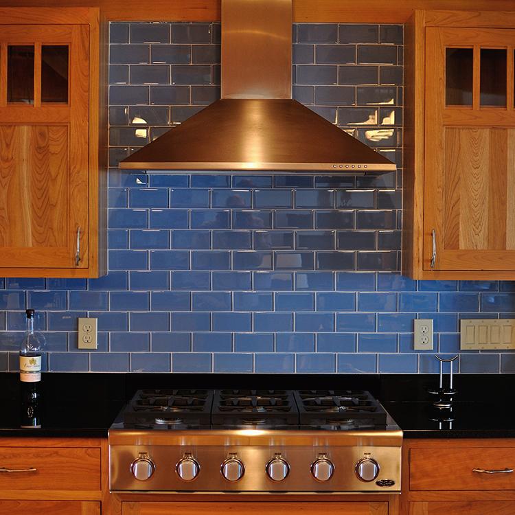 Cooking alcove, apron front rangetop, tile backsplash, chimney hood, glass mullion doors