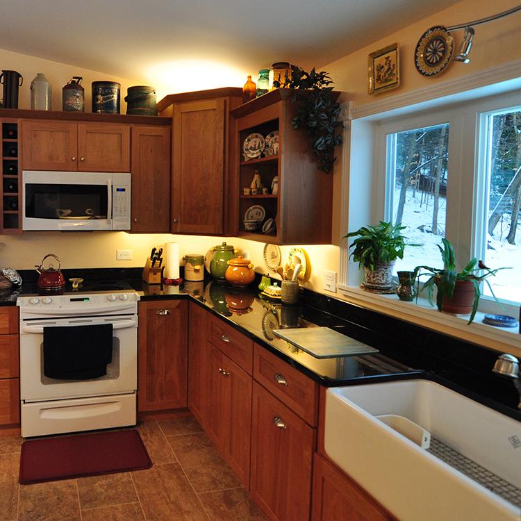 Wine cube, apron front sink, black verde granite tops, open shelving