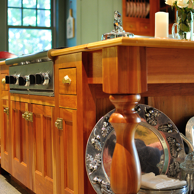 Rangefront cooktop, furniture island with turned legs, latch hardware, island end display