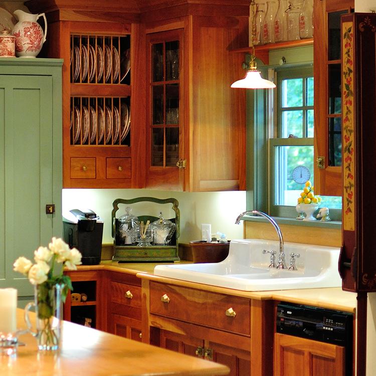 Farmhouse sink, dish racks, bump-out sink cabinet, recess doors, paneled appliances, glass mullion doors