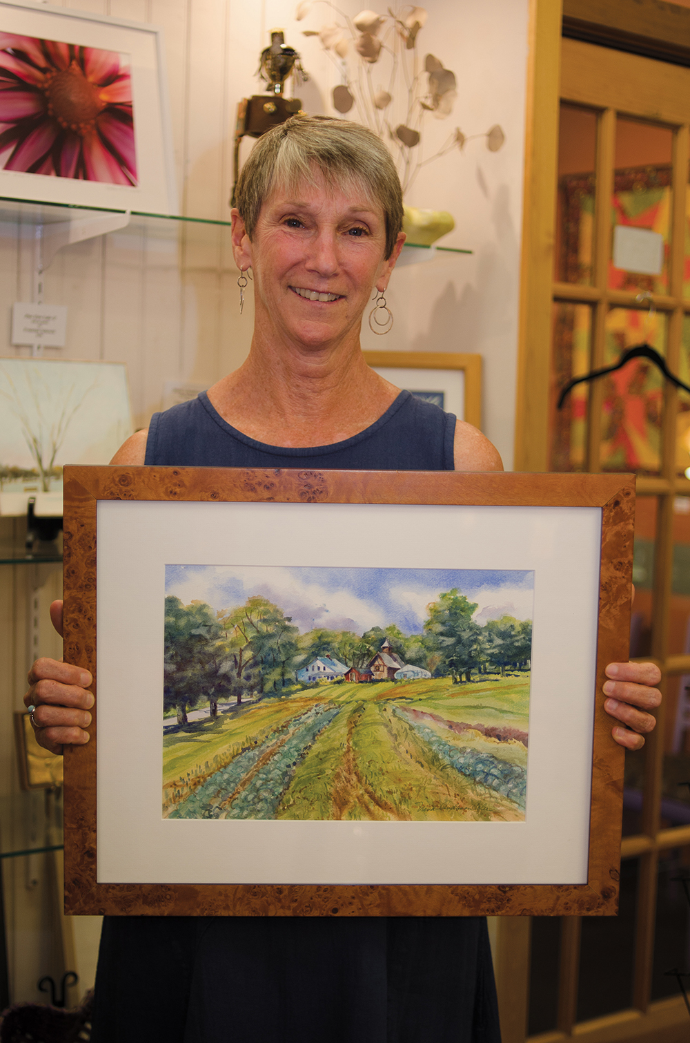 Painter Nina Anderson Coler displays one of her landscapes