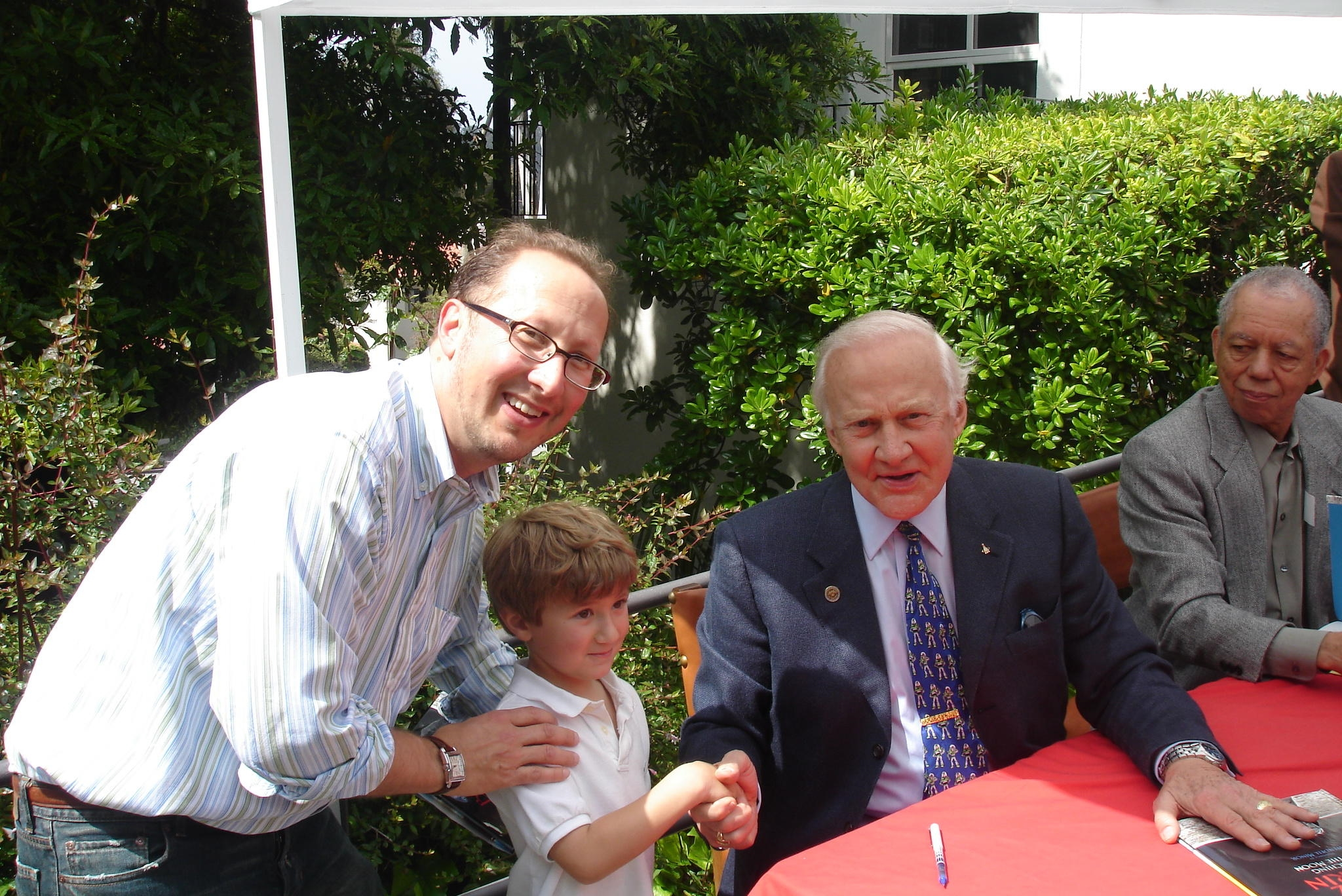 """Photo of Sam McCarthy-Potter shaking hands with Dr. Aldrin. Local designer and rocket builder, Peter Rothe quipped, """"Do not let the boy wash his hand for a week. That was the hand that landed the Eagle on the Moon."""""""