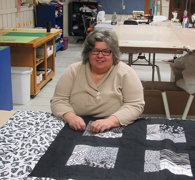 Trinity Quilters meet every Tuesday at 9 am. Anne working on tying her quilt.