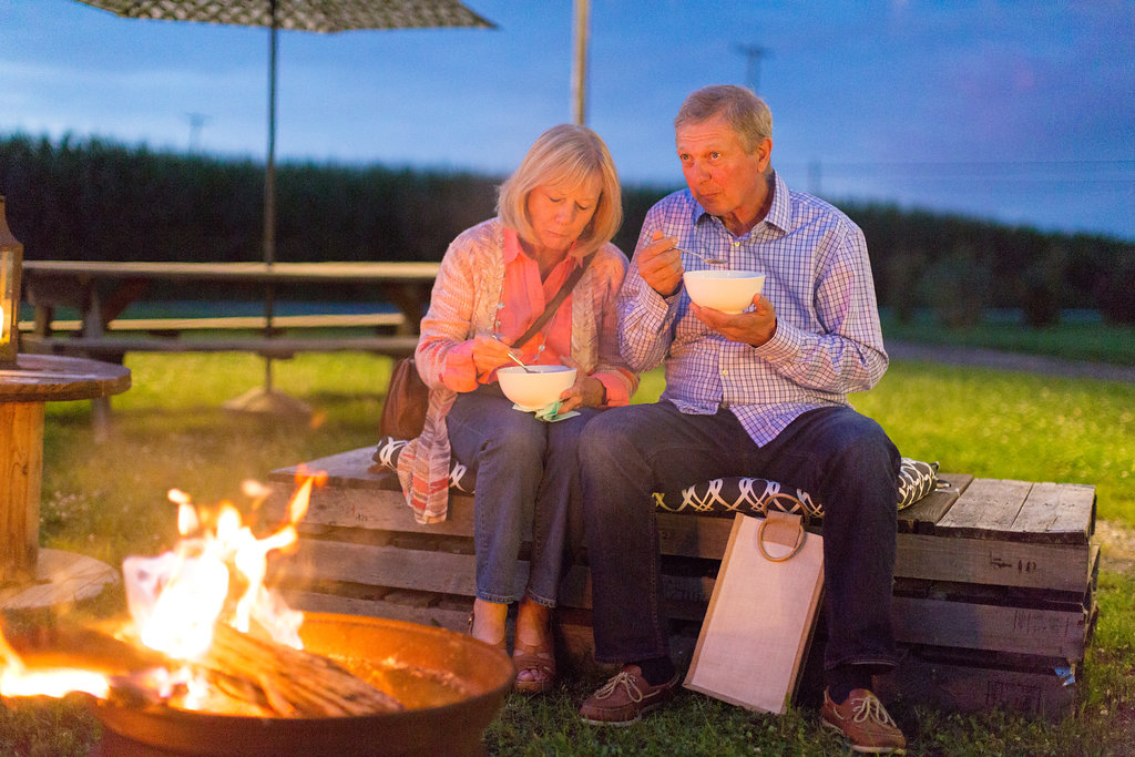 guests by the fireside at Farm to Table dinner