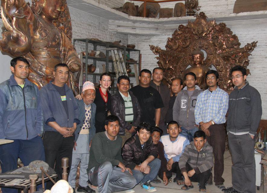 2011 Fulbright Senior Scholar Maureen Drdak with Rajkumar, Rabindra (her guru) and Rajendra Shakya, grandsons of the celebrated historic repoussé master Kuber Singh Shakya and sons of Rudra Raj Shakya (pictured standing next to Drdak third from left) in their family atelier in Imodol, Patan, Nepal in 2012. Rajkumar is standing next to Drdak (striped shirt), with Rabindra immediately next to him. Rajkumar's son Sawrup is standing far right, with Rajendra standing third from right.