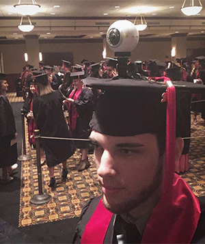 Jackson wearing the Gear 360 VR camera during his graduation ceremony at UT.