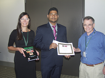 Rabrinda Mandal (center) receives the UA Center for Food Safety Foodborne Pathogens-Fundamental Understanding Poster Award. With him are Patricia Osborn (left) of Elsevier and Steven Ricke (right), director of the Center for Food Safety.