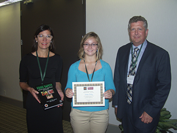 Andrea Jeffrey (center) receives the Simmons Foods Pet Food and Animal Feed Safety Poster Award (First Place). With her are Patricia Osborn (left) of Elsevier and Hank Cotney (right) of 3-D Corporate Solutions.