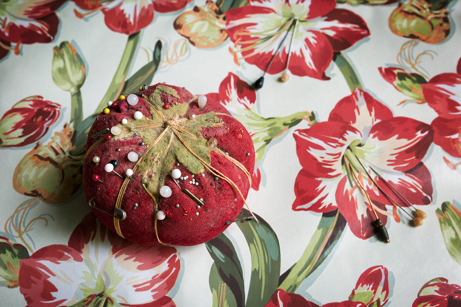 the pincushion on vintage wrapping paper with pins as stamens from the amaryllis lily