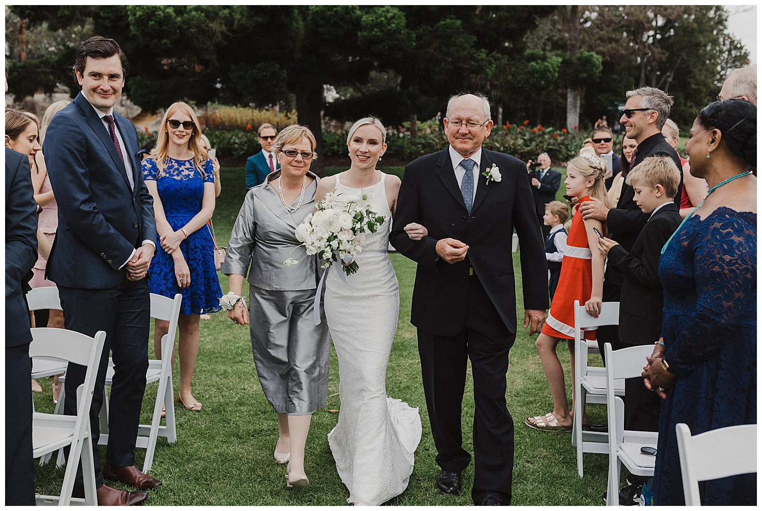 Bride walks down the aisle with her parents in the Royal Botanic Gardens