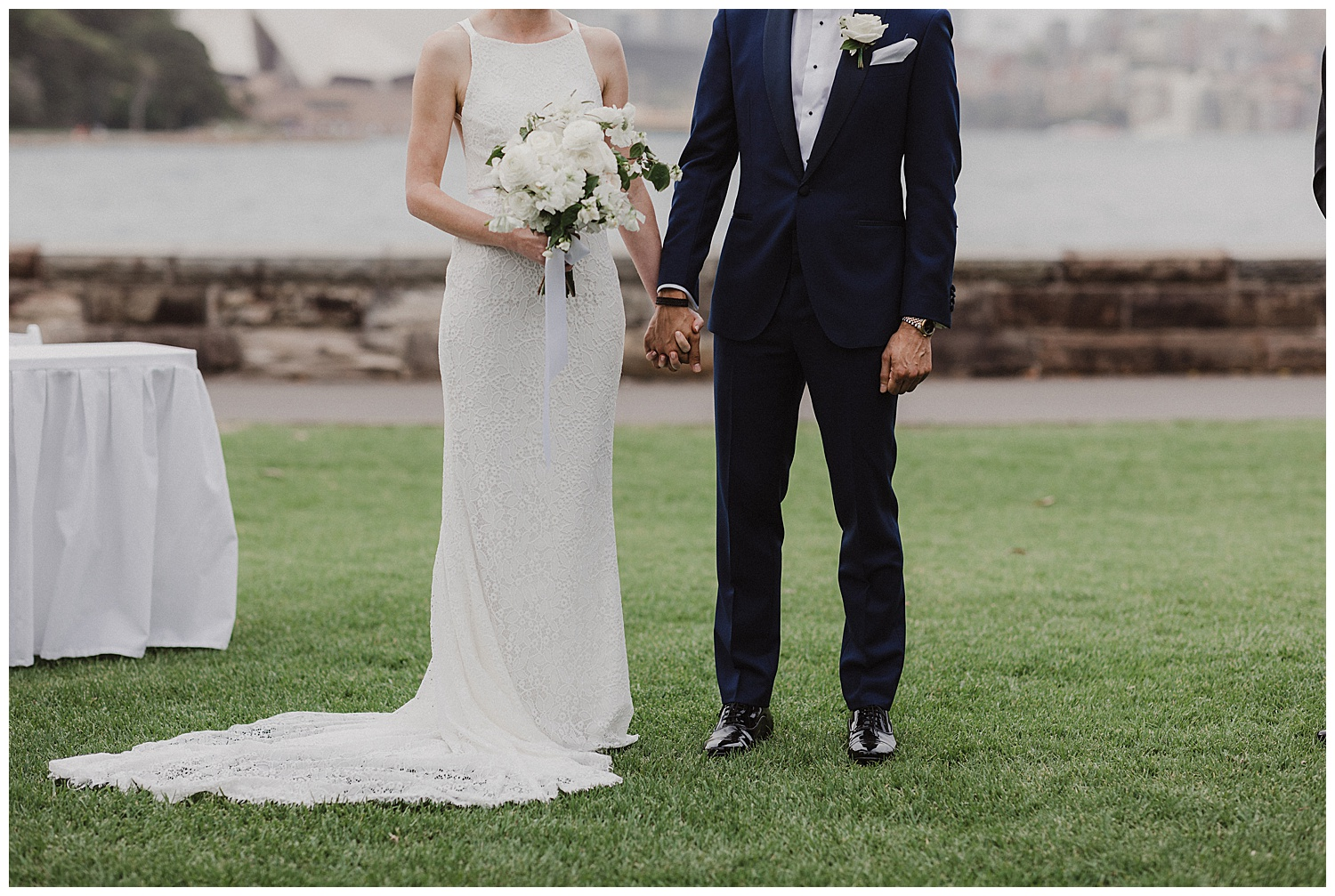 Couple holds hands during wedding. Dress by Karen Willis Holmes, Flowers by Poho, tux by The Bespoke Corner Tailor