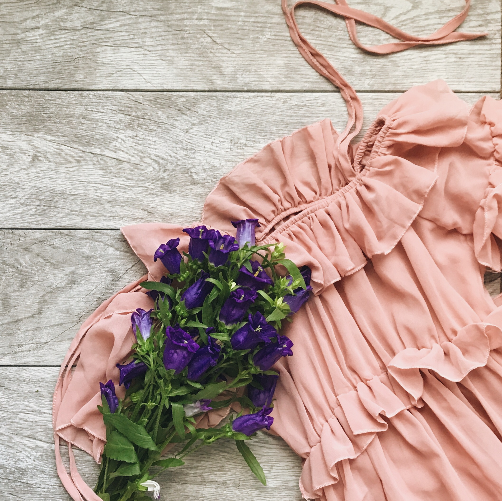 Flatlay-pink-ruffled-dress-with-purple-flowers-by-Atlanta-photographer-Chanel-French