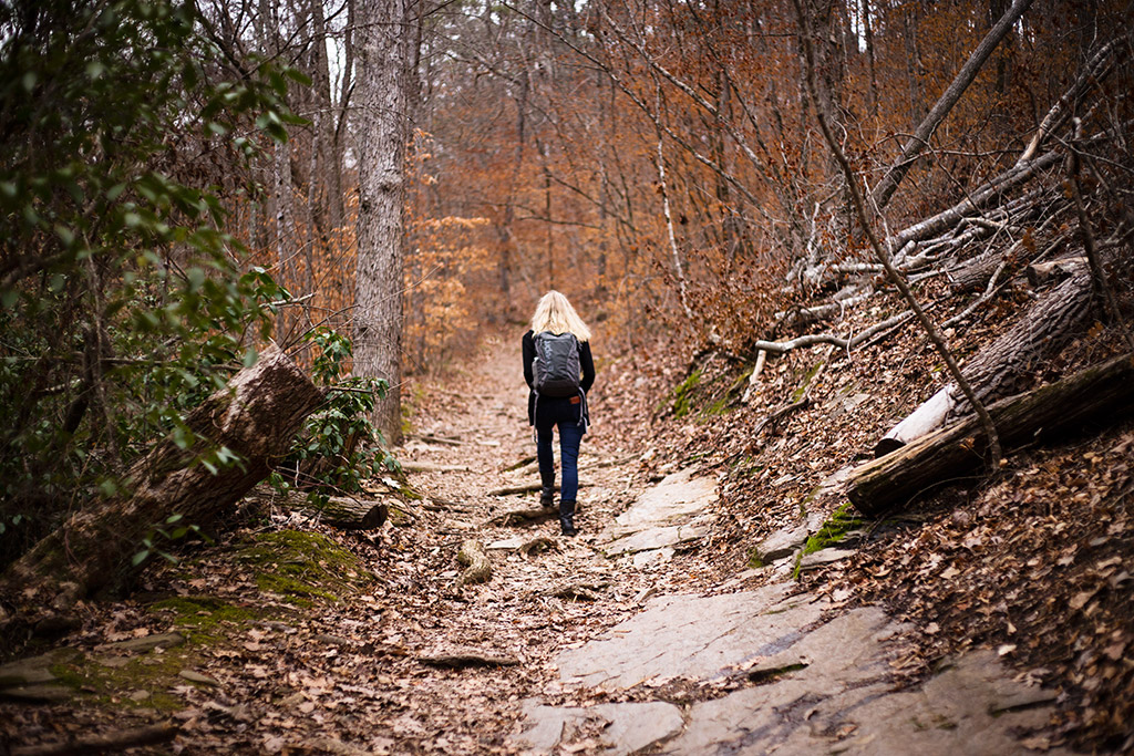 Woman-hiking-through-trees-in-fall-Sope-Creek-by-Atlanta-photographer-Chanel-French-1.jpg