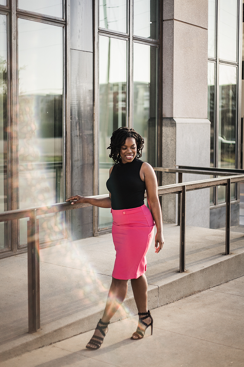 Black-business-woman-in-pink-skirt-walking-through-city-by-Atlanta-portrait-photographer-Chanel-French