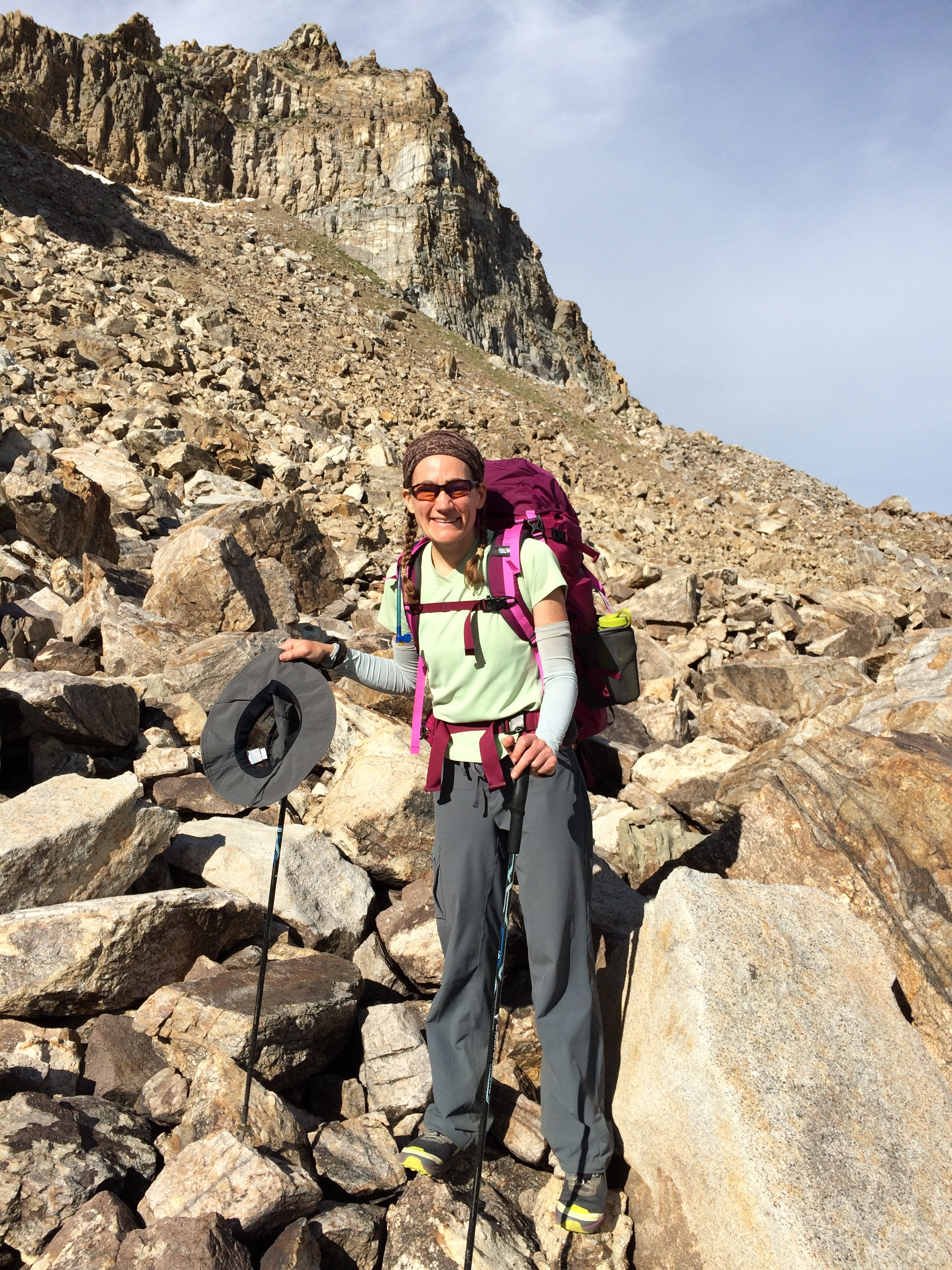 Cheri crossing the endless small talus of Mt. Fitzgerald's shoulder as the high clouds coalesce above