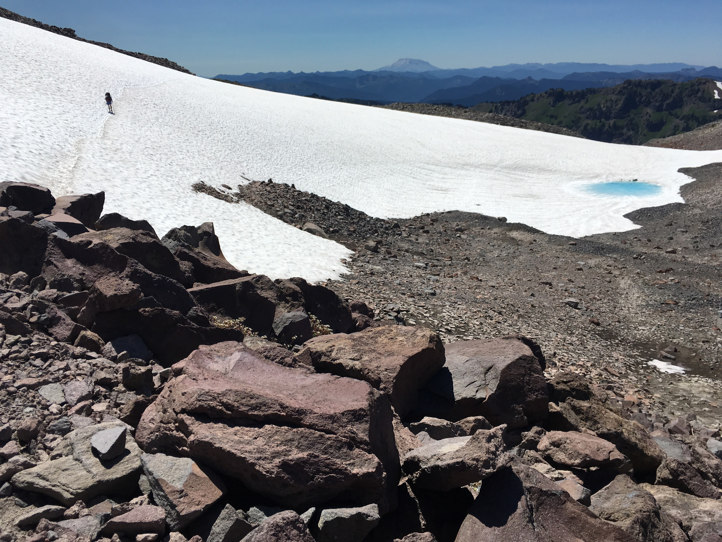 Me crossing another big snowfield with Mt St Helens in the distance