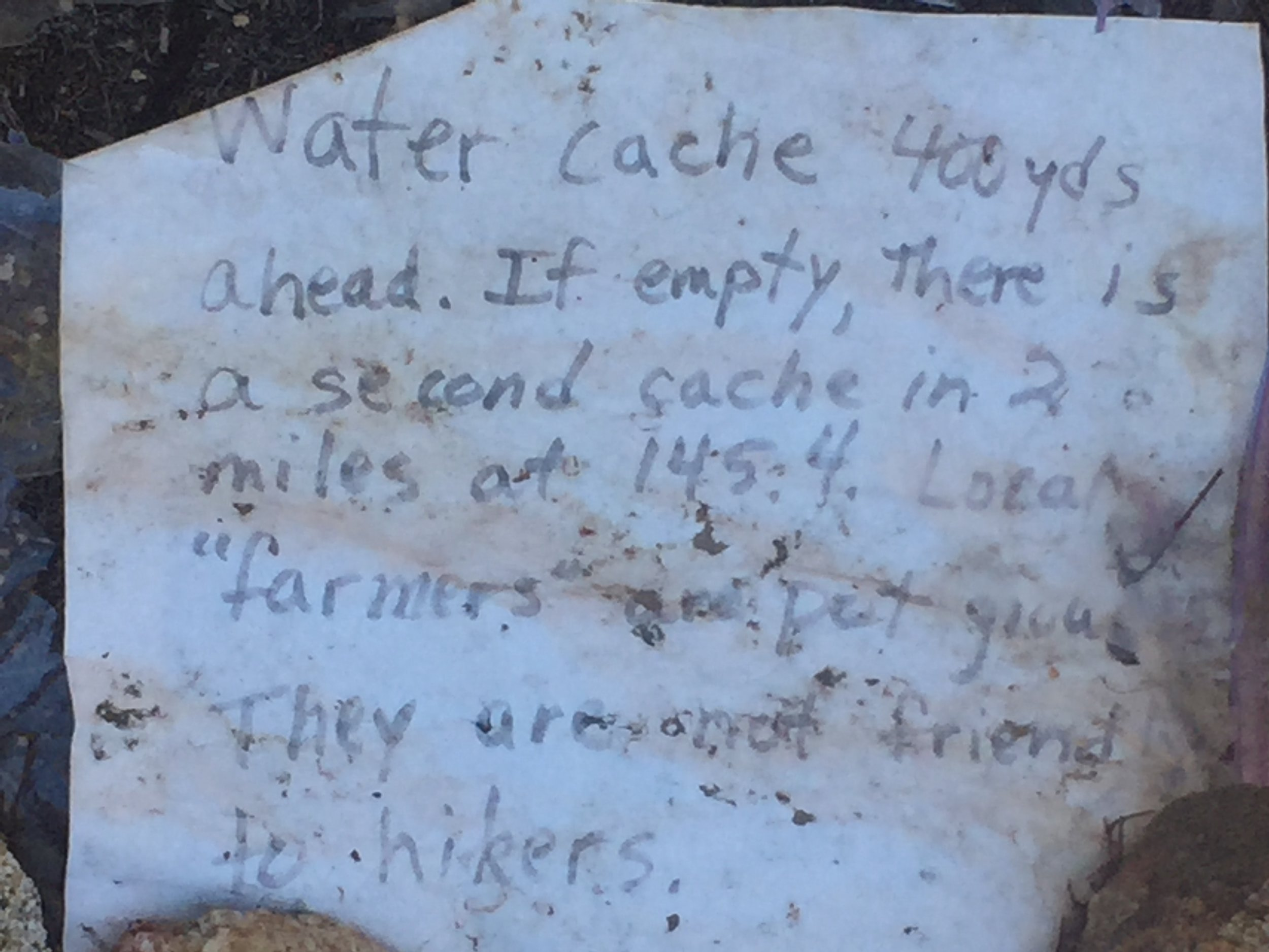 """We came across this weathered note on the trail, warning hikers about the """"farmers"""" with greenhouses"""