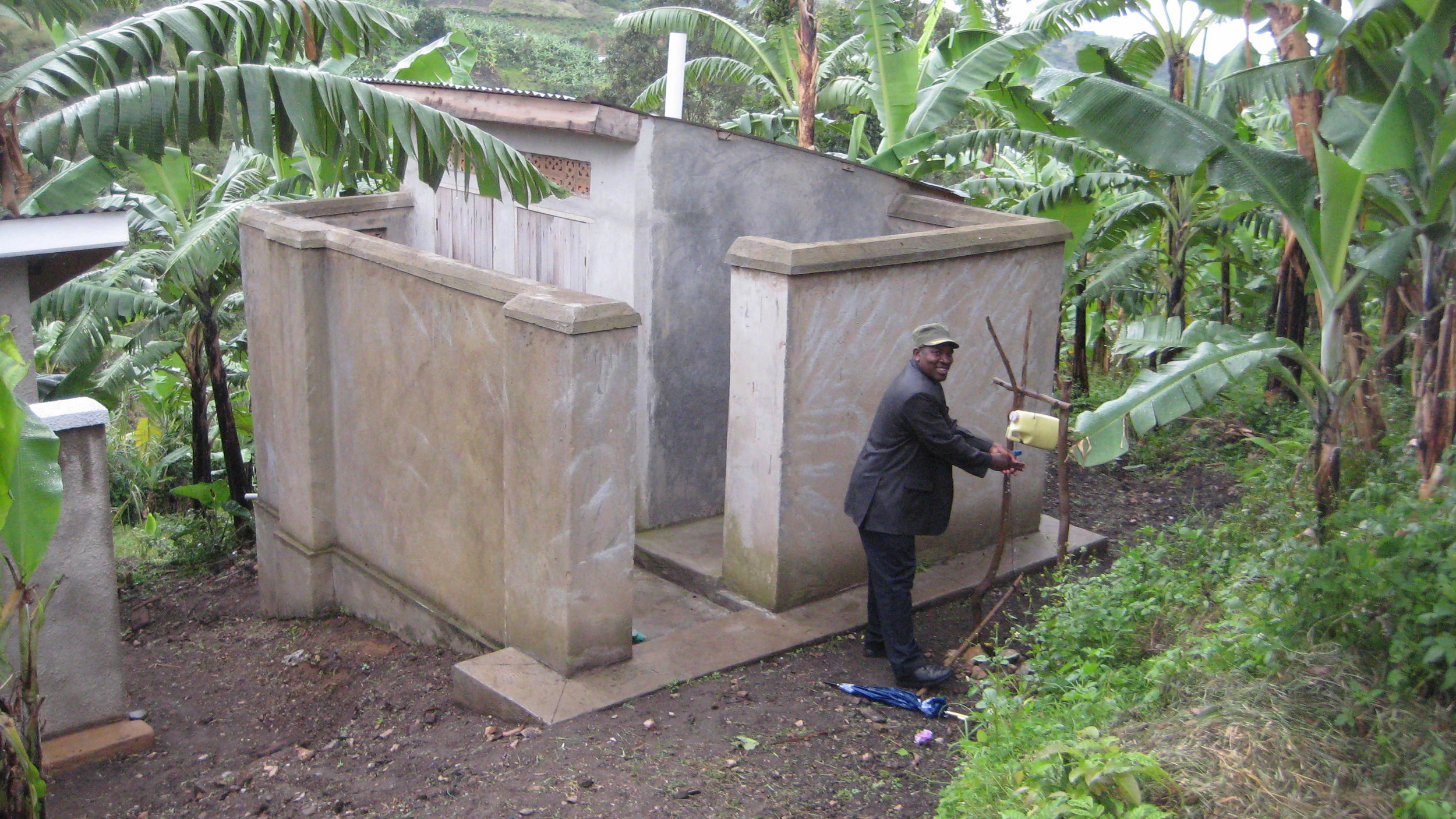 Latrines at Burema SSS with Eric at Tippy Tap.jpg