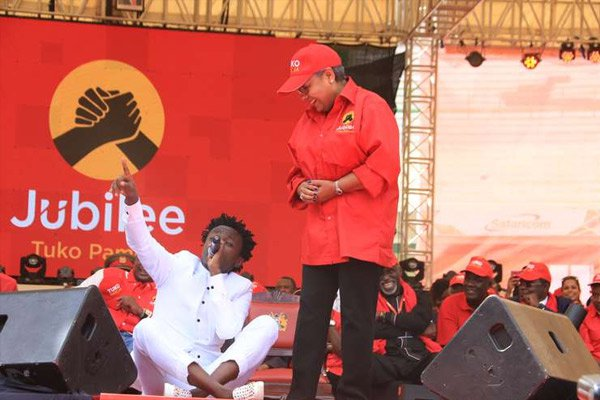 First Lady Margaret Kenyatta watches as singer Bahati performs during the launch of the Jubilee Party on September 10, 2016. The artiste's act of sitting on the President's seat as he serenaded the First Lady has drawn more discussion than what the President said at the event. PHOTO | JEFF ANGOTE | NATION MEDIA GROUP