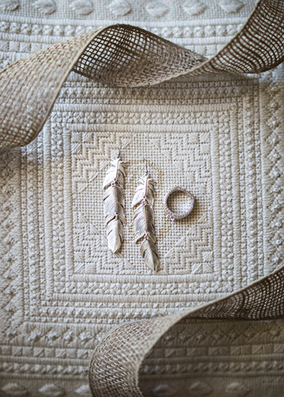 silver feather earrings and tooled silver wedding ring on quilted pillow