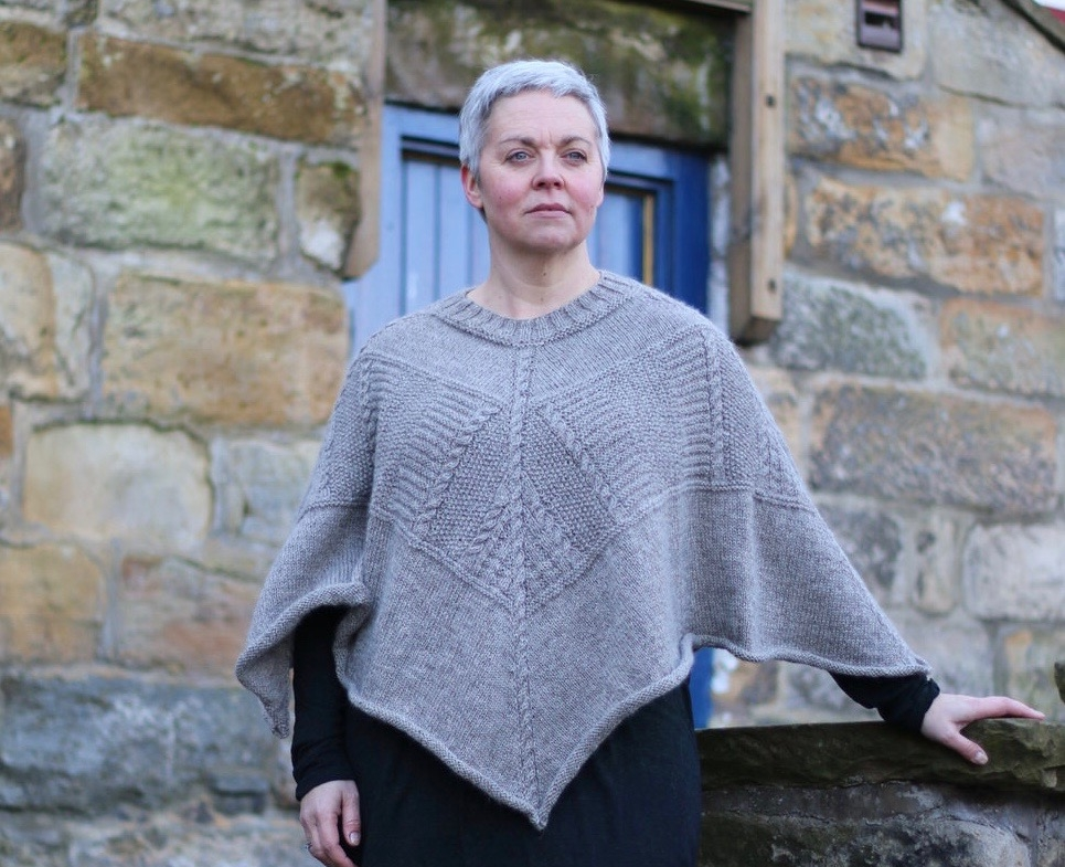 """Saltwick Bay poncho  This cosy poncho combines traditional motifs from three gansey locations  Yarn: Dovestone DK (252 yds / 230m in 100g)  Yarn Quantities: 1258 yards (1150 m)  Needles: 4mm circular 80-150cm lengths, 3.5mm x 60-80cm circular and DPNs  Notions: cable needle, stitch markers  Size: one size - hem circumference 165cm/65"""", Length 51cm/20"""""""