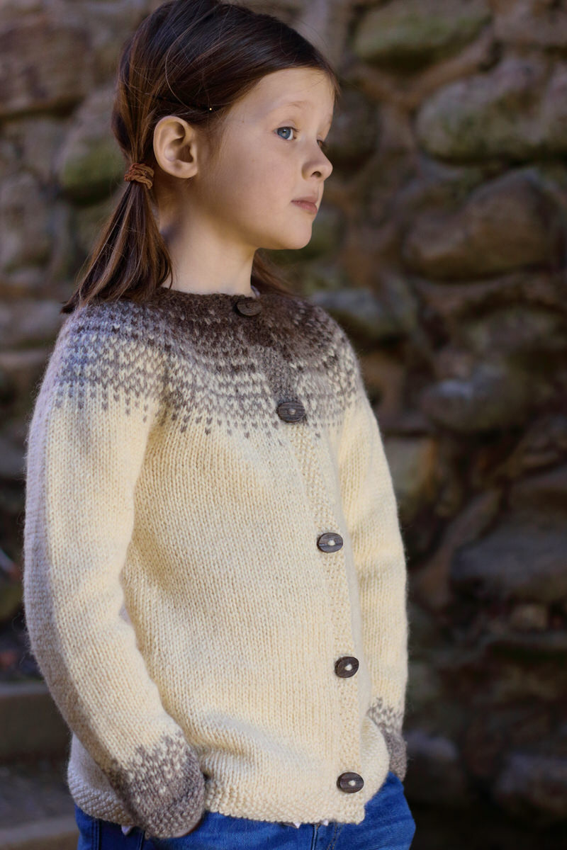 """Hiro Petite by Julia Farwell-Clay    Yarn: Baa Ram Ewe's Dovestone Natural Aran (170m in 100g)  Yarn Quantities :3-4 skeins MC, 1 skein each CC1 & CC2   Needles : 5mm x 60cm circular and DPNs, 4mm x 60cm circular and DPNs  Notions:  stitch markers, 5-6 x 20cm buttons  Sizes: 4 (6, 8, 10, 12, 14) years. Finished Chest:23 (25, 27, 29, 31, 33)"""""""