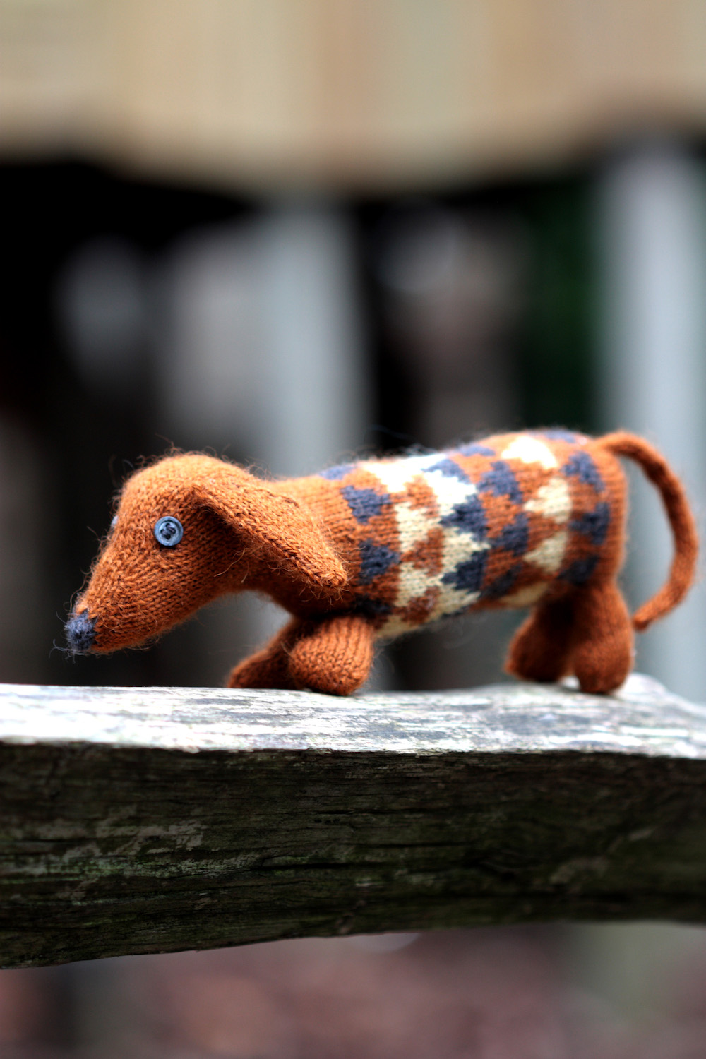 Dashing Dachshund by Ella Austin  Yarn: Baa Ram Ewe Titus (70% Wool, 30% Alpaca) 320m per 100g hank Kit includes: - Pattern leaflet - Mini hanks of Titus in colours Parkin, Filey and Coal - Toy stuffing - Tapestry needle for sewing up - 2 buttons for eyes You will also need: - 2mm DPNs - stitch marker Your finished dachshund will be about 22cm long and 9 cm tall.
