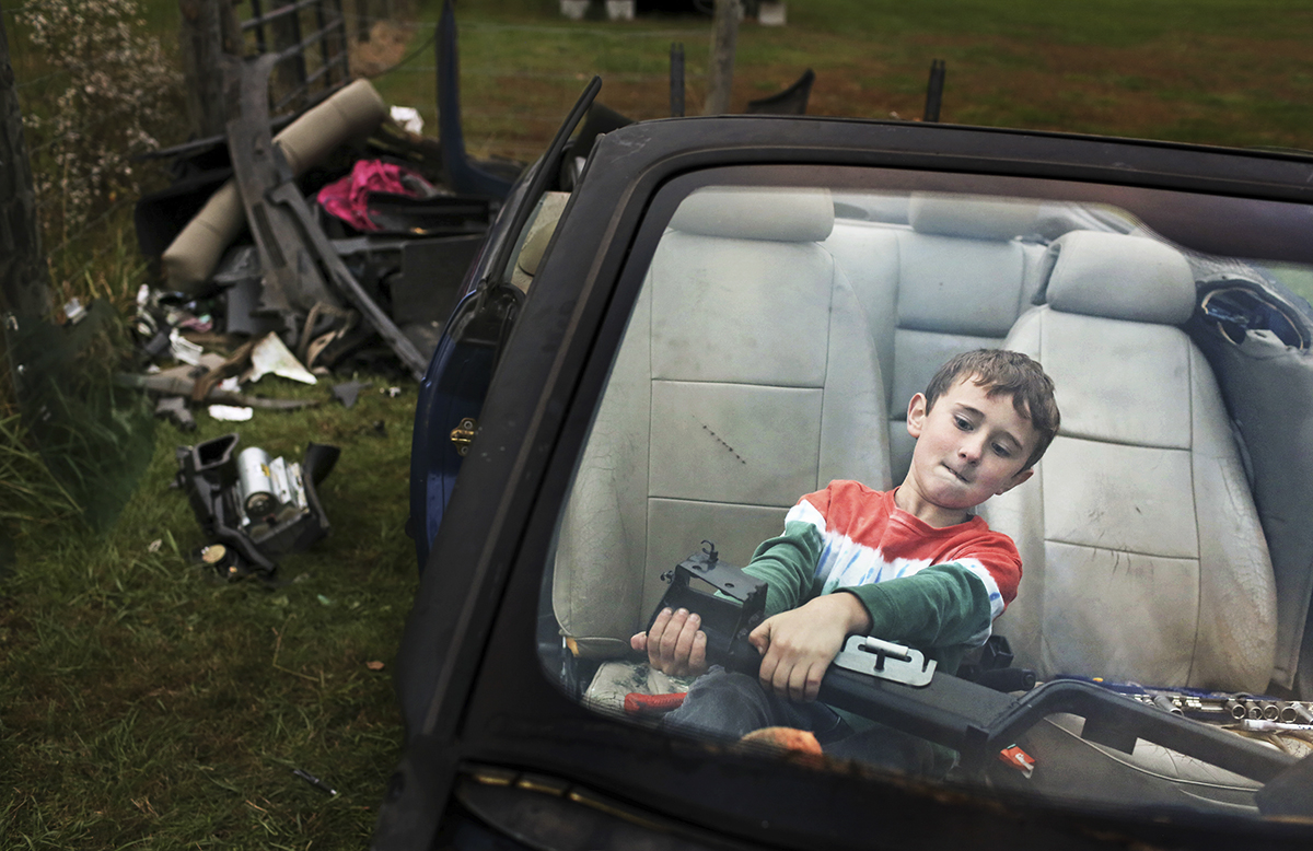 Blake Hendrix, 8, attempts to remove a part of the dash from an old Saab in the front yard of his home outside of Berea, K.Y.. Blake is helping to strip the car for parts to sell with his two brothers and two friends.