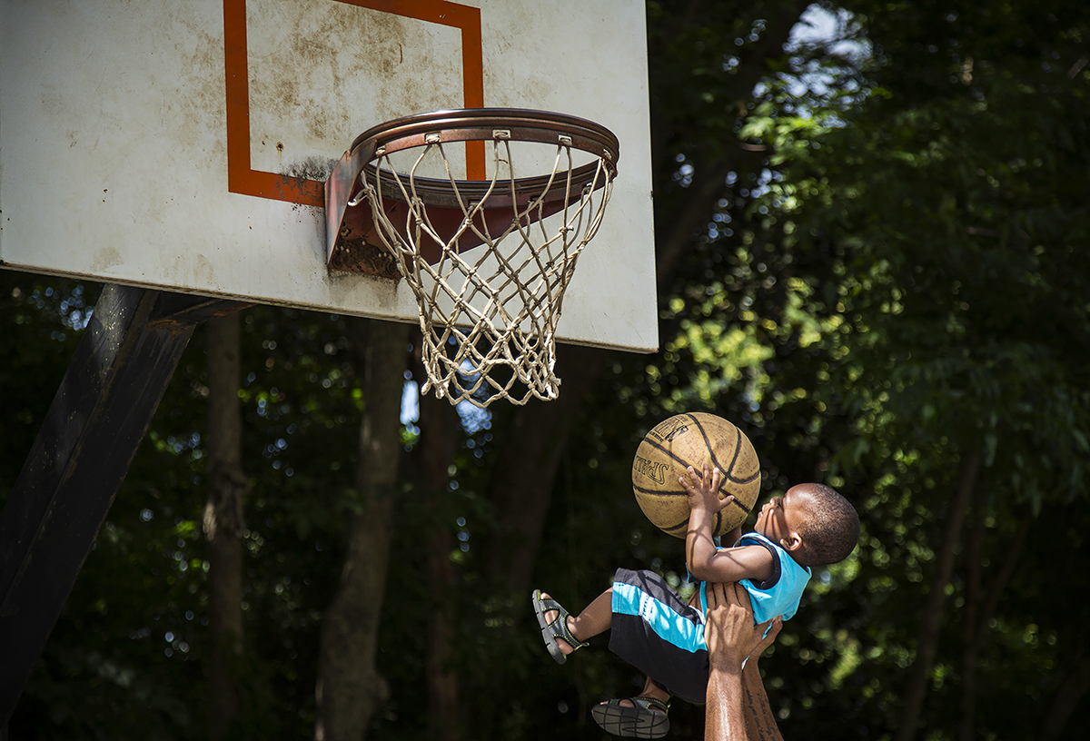 18 month-old Zyhier Gregory is lifted up by his uncle Derrick Conor to shoot a basket while playing basketball with his family in Freedom Park in Charlotte, N.C. on Saturday, June 13, 2015. Zyhier's father Darius Gregory says that Zyhier is learning to play basketball on his Fisher-Price basketball goal at home.