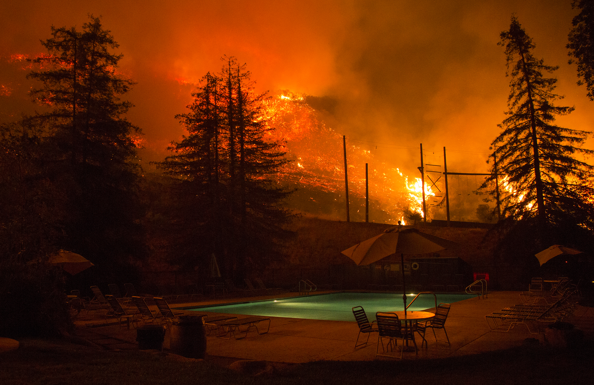 Flames approach a pool in the El Capitan Canyon camp as firefighters battle the Refugio fire in Santa Barbara, CA on Thursday, June 16, 2016.