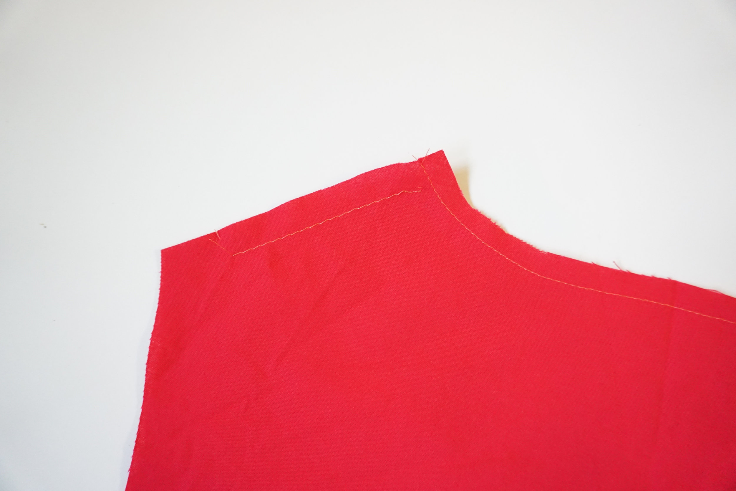 Step 4: Sew an ease stitch at the shoulder seam on the BACK BODICE between the circle and notch.  EASESTITCH : stitch along the seamline, using a basting stitch. Pull thread ends when adjusting fit.