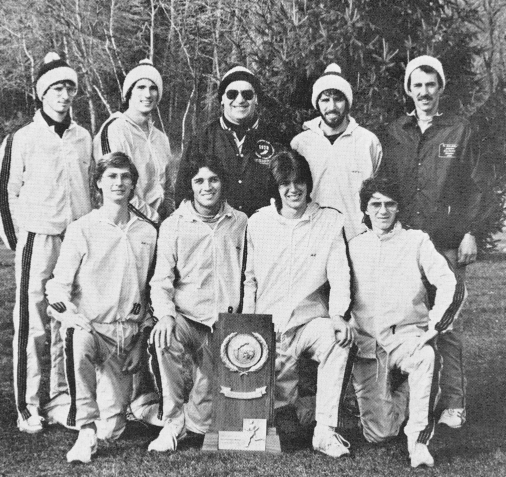 Coach Cy Fritz (dark jacket, center) and Assistant Coach Jeff Bradley (dark jacket, right) with their cross country runners after winning the NCAA DII National Cross Country Championship in 1981. FRONT ROW (kneeling, left to right): Erik Steudel, Don Williams, Greg Cauller, Bill King SECOND ROW (standing): Gary Owens, Andy Calsmer, Coach Cy Fritz, Paul Bowman, Assistant Coach Jeff Bradley