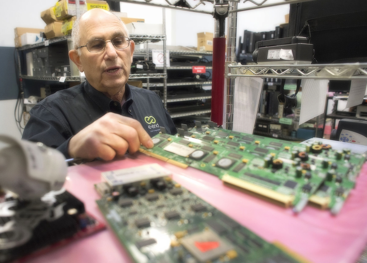 Steve Chafitz, of e-End in Frederick with electronic circuit boards that have been removed from computers for recycling.