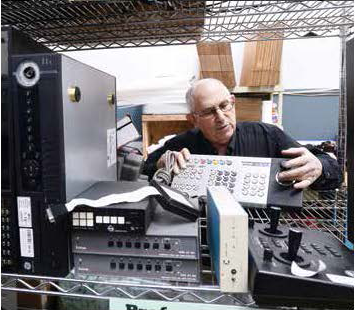 E-End President Steve Chafitz looks through other electronics in his warehouse that could be refurbished, which his company's certification requires them to do whenever possible.