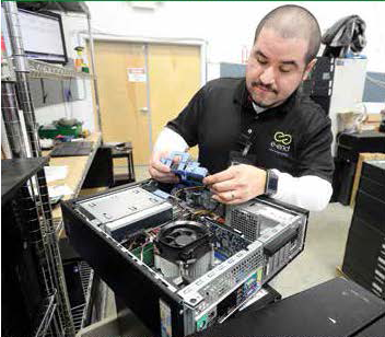 Victor Segura tests a PC desktop before it goes into the Good Used Electronics retail area at e-End, which is a Registered Microsoft Refurbisher.