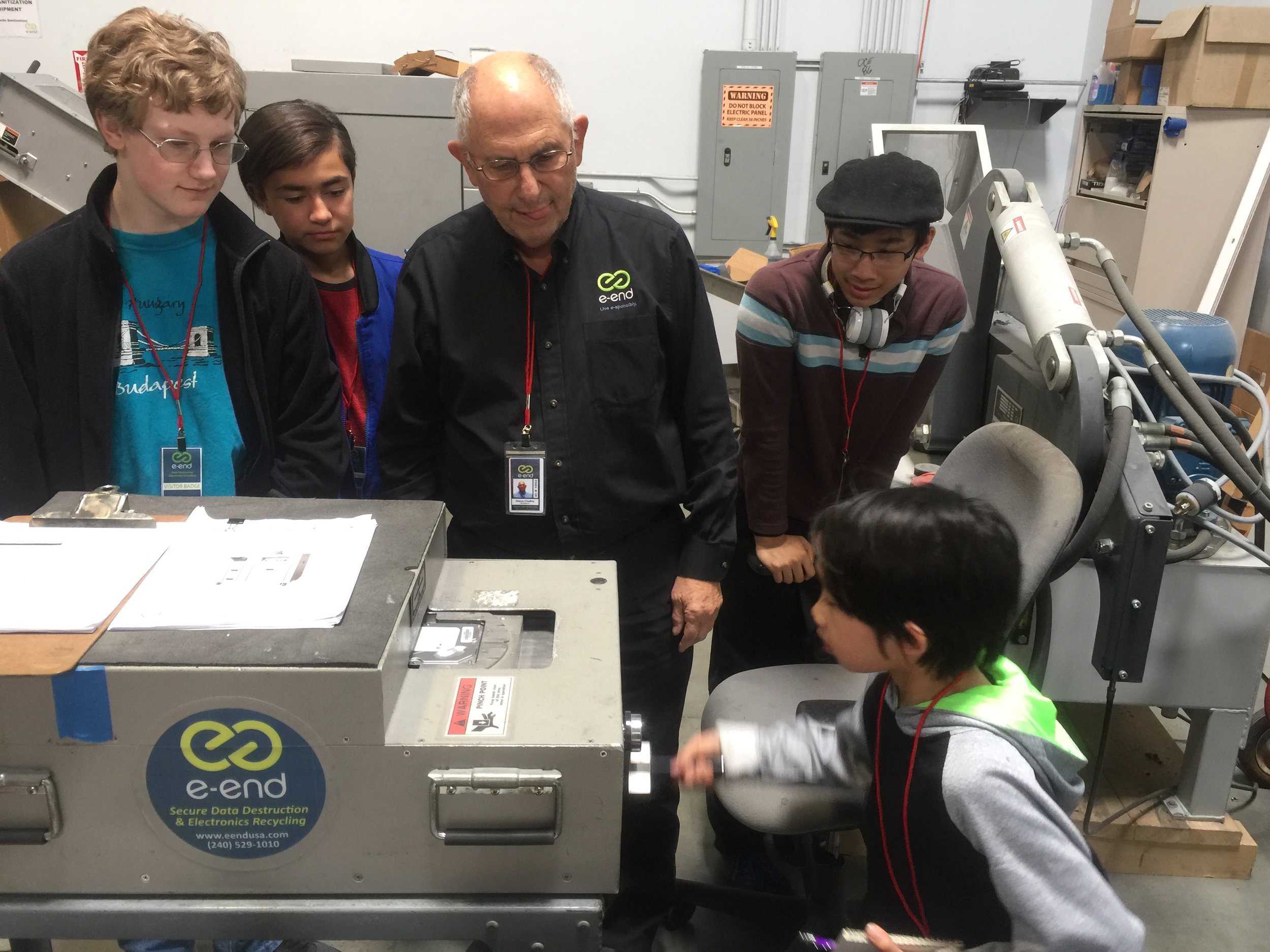 Student using the HM-1 manual-powered hard drive degausser, during facility tour with e-End President, Steve Chafitz.