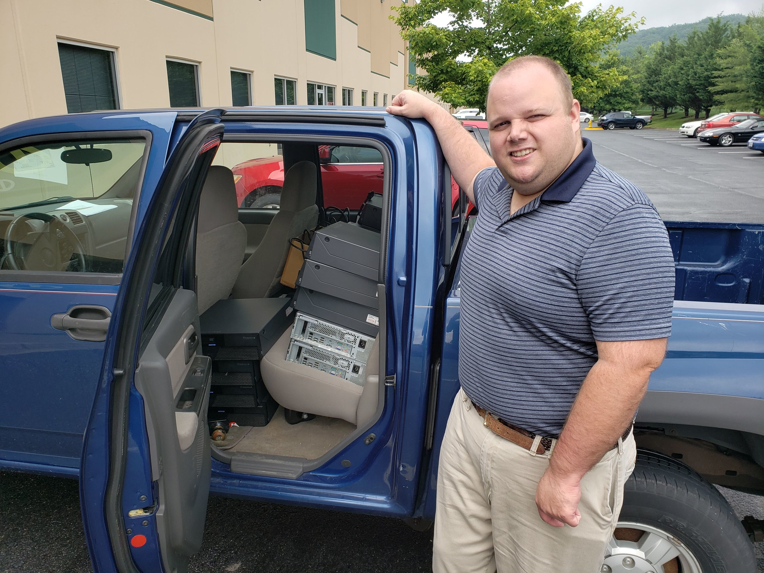 Eric D. Zimmerman, founder of The Buddy Project,pictured with computers that e-End donated to his organization.