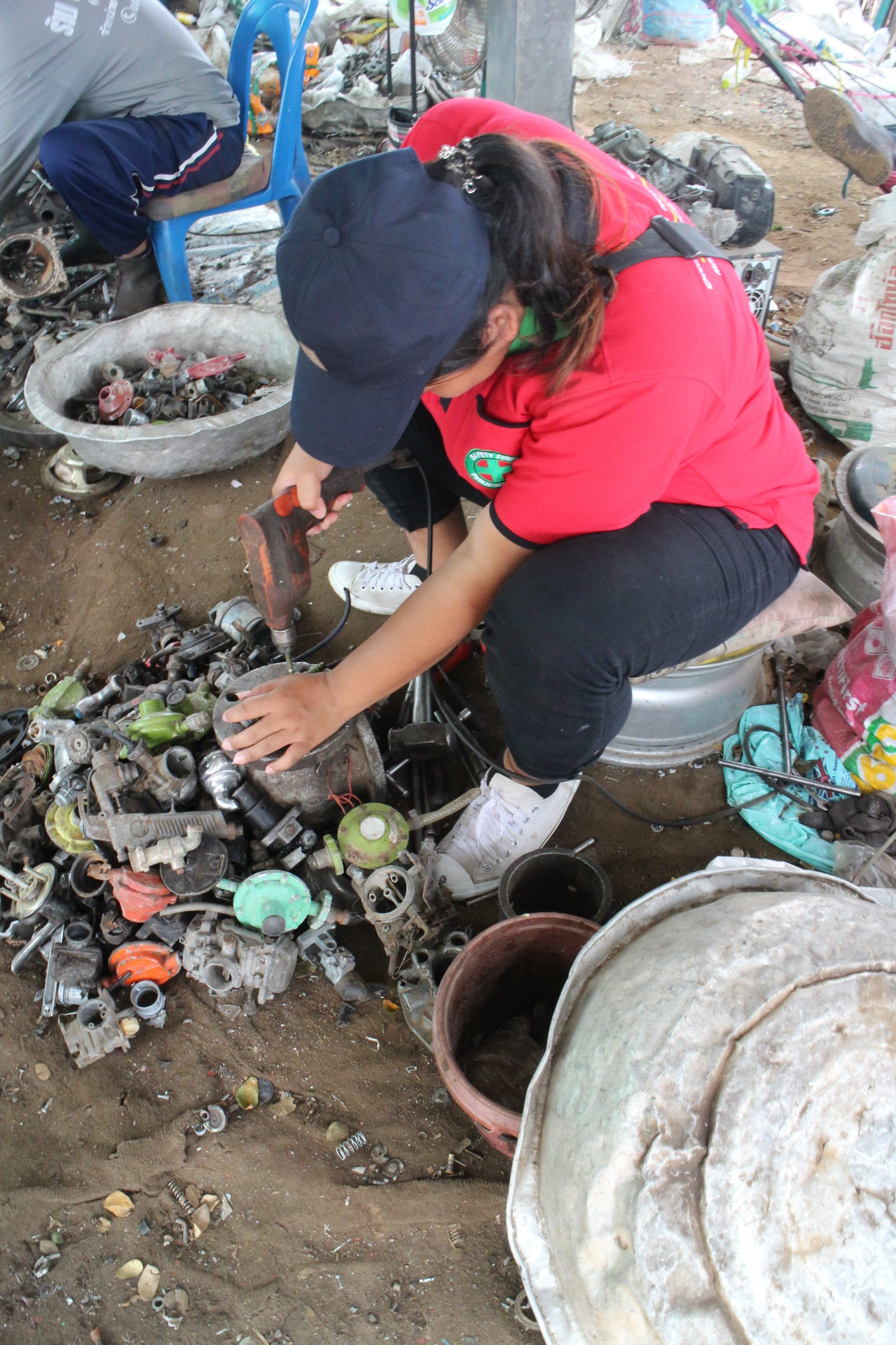 An e-waste recycler works to take a motor apart in Thailand. Image credit: University of Michigan
