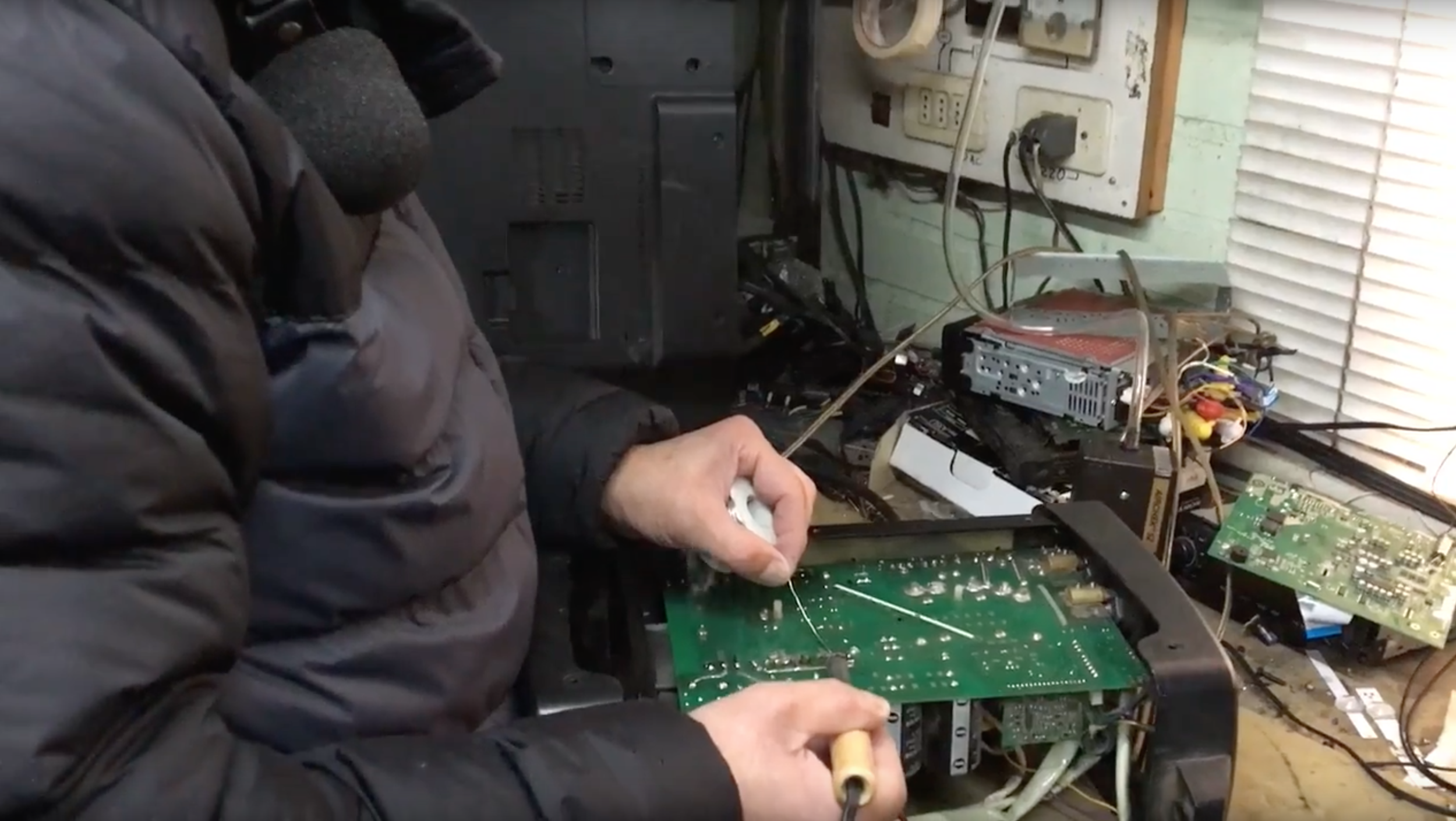 A e-waste recycler solders a printed circuit board in Chile. Image credit: University of Michigan
