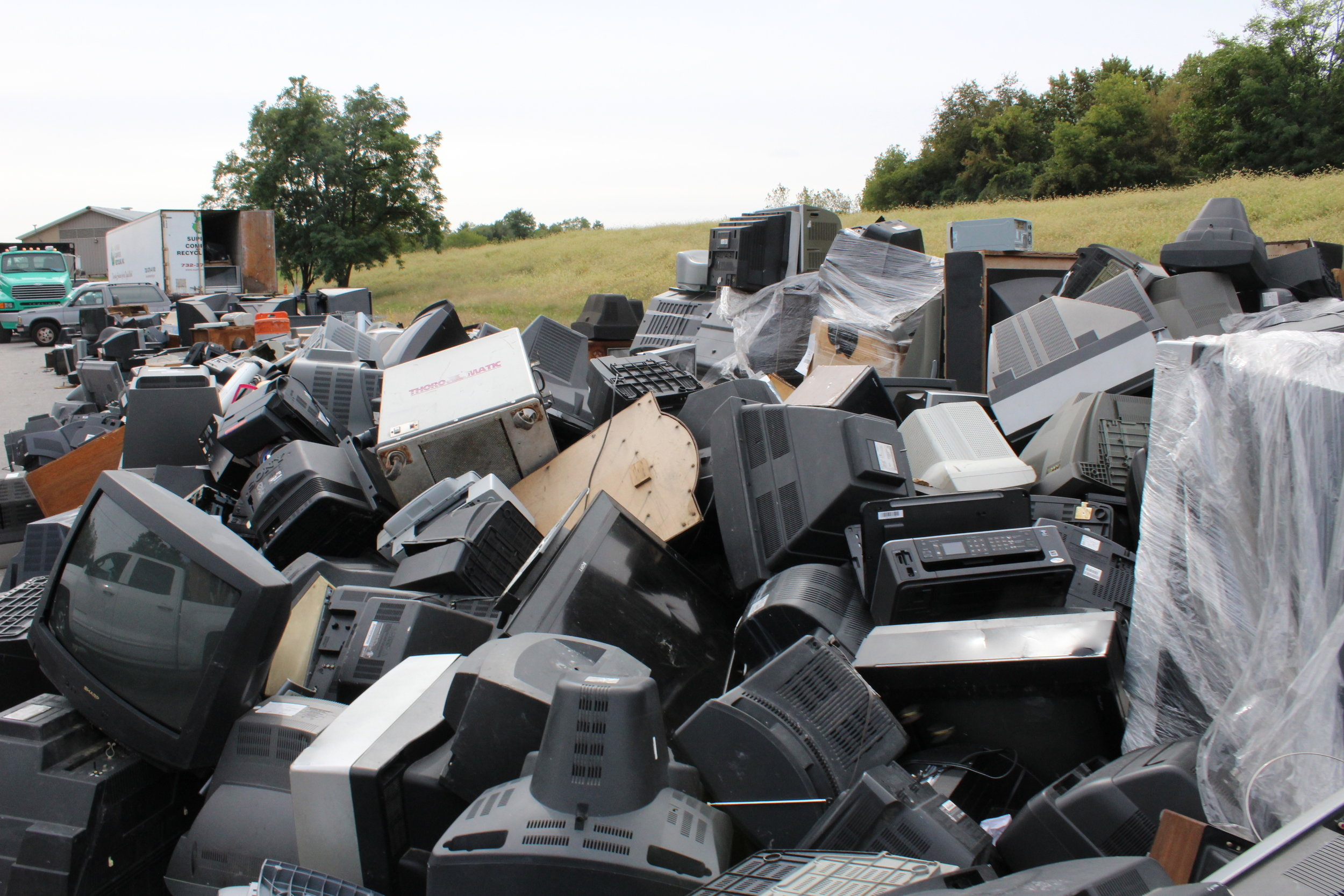 A collection of E-Waste -Piled up old CRTs, stereo equipment, and computer systems.
