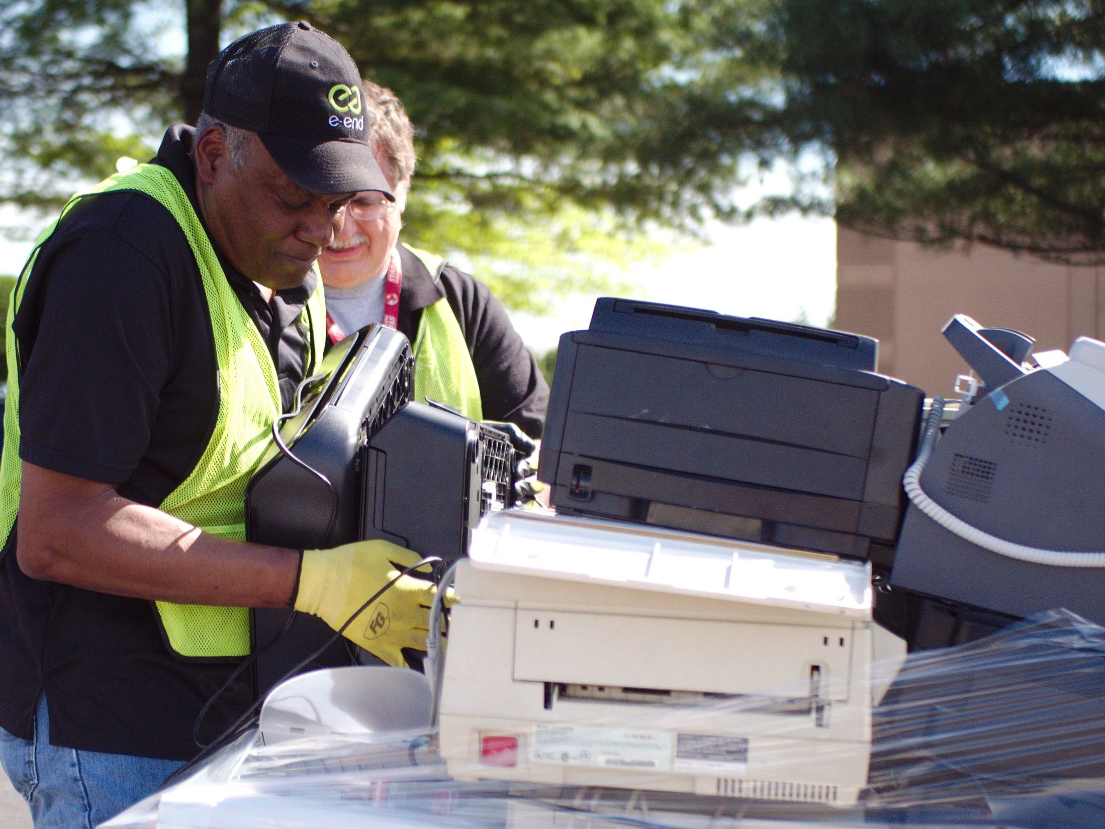 e-End employees stacking small printers during an electronics recycling collection event.