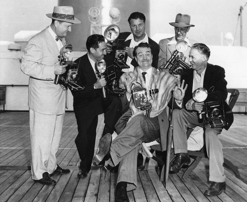 Comedian Red Skelton with photographers aboard S.S. United States.