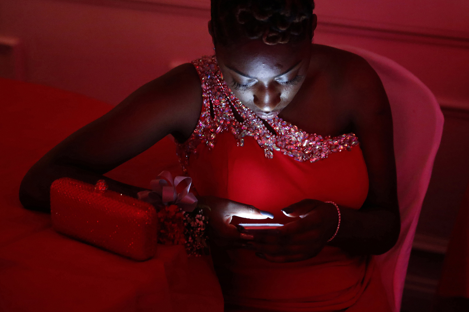 Red Prom - A senior at Irvington High School takes a break from dancing to check her phone during their prom at the Gran Centurion Ballroom in Clark. Wednesday May 20, 2015. Clark, NJ, USA