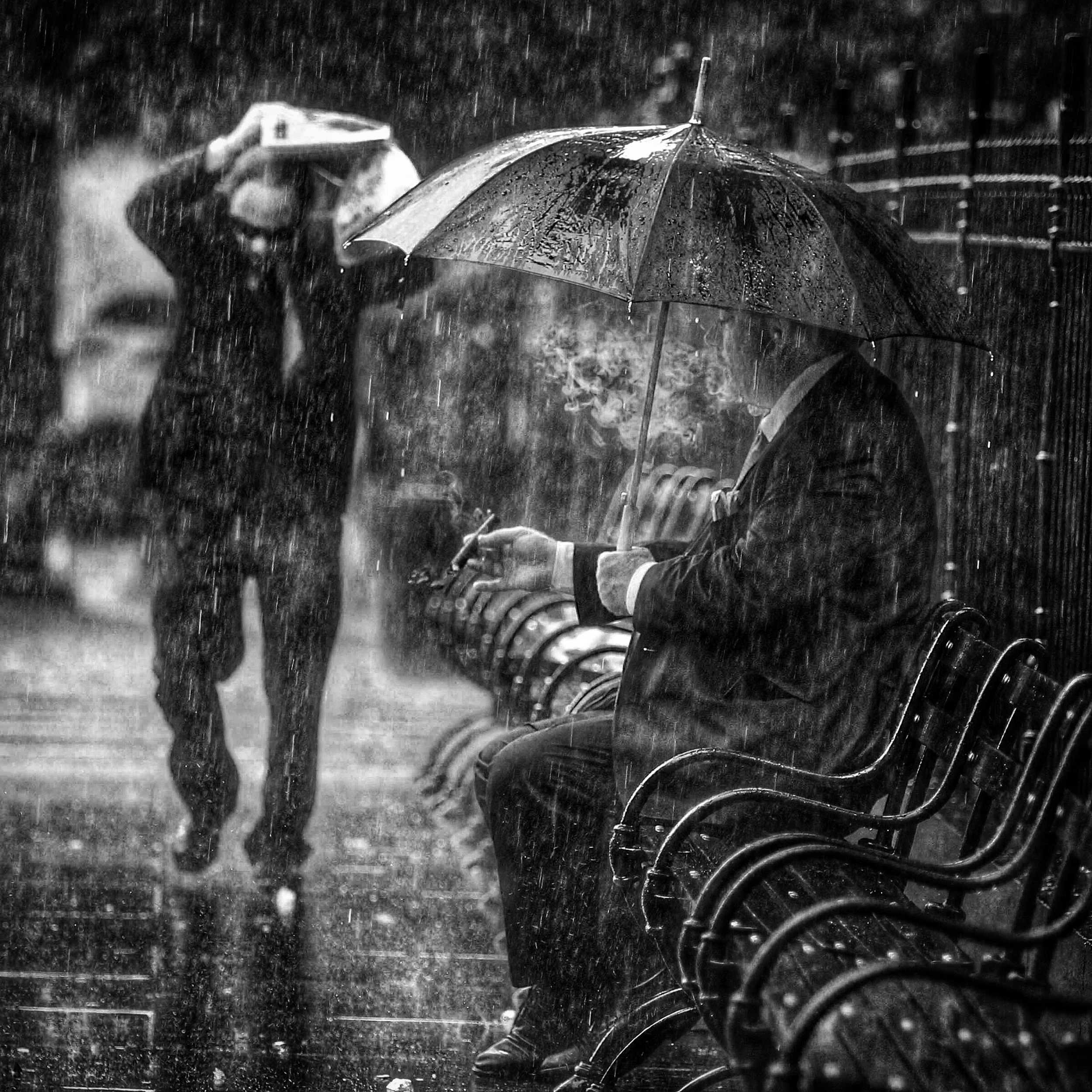 """A man who refused to be identified smokes a cigar under an umbrella on a bench as others are caught in an afternoon downpour Thursday, July 30, 2015, near City Hall in New York. After days of temperatures above 90 degrees the rain was expected to break the heat wave. The man said, """"It's always 85 and sunny with a cigar."""""""